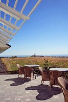 Rattan chairs and table on sunny terrace below slatted porch against wide view of landscape