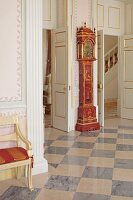 Antique grandfather clock with gilt embellishments against wall between two open doors and chequered floor in foyer of stately home