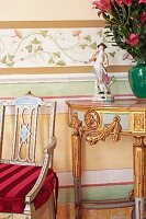 Antique chair next to classic console table with gilt carvings against wall painted with stencilled motifs