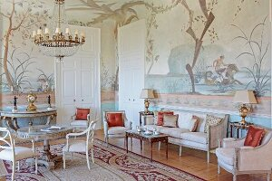 Period furniture in stately home salon - upholstered chairs around round, solid wooden table and console table against wall painted with mythological motifs