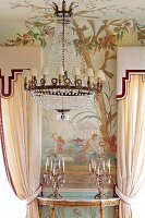 Chandelier with small white lampshades in front of painted wall and candlesticks on gilt console table