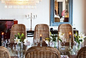 Candlesticks and arrangements of lilies on lustrous glass table surrounded by wicker chairs with curved backs
