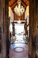 View through rustic wooden door into temple-like interior with large chandelier