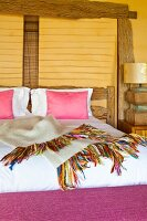 Pink scatter cushions on bed against yellow wall with rustic wooden beams