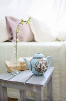 Chinese teapot, flowering twig and books on stool next to bed