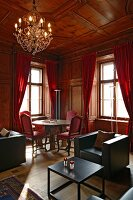 Historic, wood-panelled salon with modern lounge furniture and antique table and chairs in front of red curtains