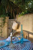 Weinglas und Flasche auf gefliestem Tisch vor Gartenmauer