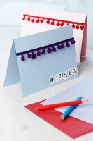 Invitation cards decorated with pompom trim
