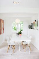 Modern, white kitchen table and Bauhaus-era shell chairs in dining room