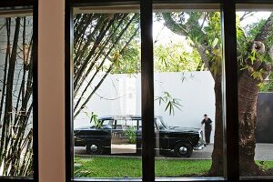 View through window of black, classic saloon car and person dressed in black in front of high, white wall