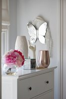 Flowers, vases, box and female hand as jewellery stand on white chest of drawers