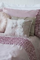 Pale pink bedspread, pillows and scatter cushions on bed
