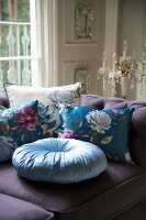 Floral scatter cushions on purple sofa