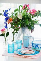 Blue glasses, napkin dispenser and painted ceramic crockery in front of vase of summer flowers