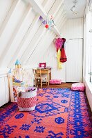 White painted wood panelling and red and blue kilim rug in girl's bedroom with sloping ceiling