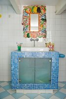 Mirror frame with vegetable motifs above masonry washstand with blue mosaic tiles