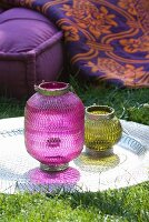 Oriental lanterns on silver-coloured tray on lawn; cushion and floral blanket in background
