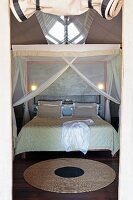 Round carpet on a wooden floor and double bed under a mosquito canopy in a spacious sleeping tent