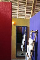 Walls painted in contrasting colours, towel rack and mirror below light roof structure of wood and bamboo