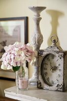Antique table clock, candlestick, hydrangea flower and scented candle on shelf