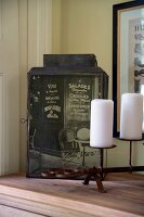 Antique lantern covered with printed photo motif and white pillar candles on candlesticks