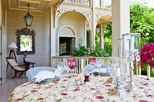 Set table with elegant candle lanterns on veranda of white, colonial-style building