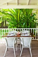 White rattan chairs around table with place settings on wooden floor of veranda with tropical, bushy palm in background