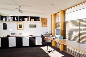 Spacious home office with wall length desk in front of a wall of windows; pictures and sculptures above base cabinets with black and white doors