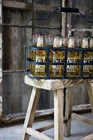 Full bottles in black metal, vintage bottle carrier on rustic wooden stool