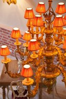 View of artistically carved chandelier with fabric lampshades