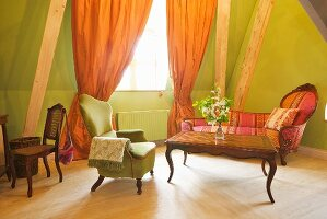 Tasteful seating area with re-upholstered antique furnishings in spacious attic hotel room