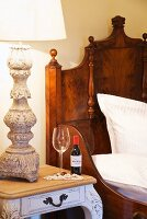 Carved lamp base, glass and inviting bottle of red wine next to solid wood, antique bed in hotel room