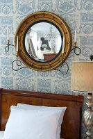 Round framed mirror on wallpapered wall with candle holders on the bed with wooden headboard