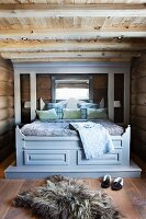 Fur rug on floor in front of rustic double bed with grey-painted canopy frame in bedroom in log cabin