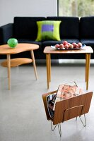 Magazine rack and 50s-style wooden side tables in front of modern sofa