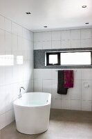 Modern bathroom with free-standing bathtub against white-tiled wall with ribbon window