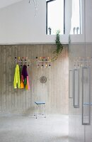 Coat racks with colourful balls on exposed concrete wall in modern foyer