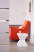 Seating area with sculptural, plastic side table and armchair with orange upholstery