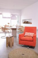 Orange armchair and wooden designer stool in front of round dining table and cantilever chairs
