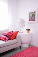 Pale sofa and white side table with designer table lamp combined with colourful scatter cushions and pink rug