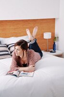 Young woman with magazine lying on front on double bed with wood-grained headboard