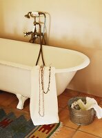 Toiletries on terracotta floor next to vintage, claw foot bathtub with brass tap fittings