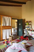 Toys in yellow-painted bedroom with child's car in front of open door