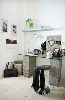 Improvised home office - glass table top on breeze blocks and designer stool in corner of room