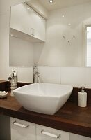 Designer washstand with basin on dark wood counter in front of simple wall-mounted mirror