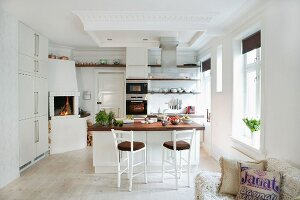 Central island with bar stools in open-plan kitchen with corner fireplace