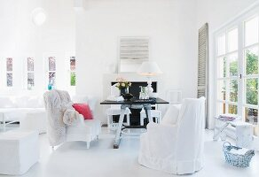 Bright living room - armchairs with white loose covers and rustic table opposite terrace door