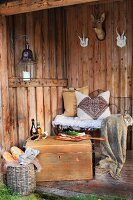 Cosily furnished shelter in woods with cushions on wire bench and simple lunch on wooden trunk