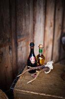 Bottle of champagne, bottle of olive oil and small set of antlers on wooden trunk