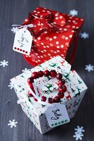 Festive, folded card gift boxes with name tags, glittery star and wreath of rosehips